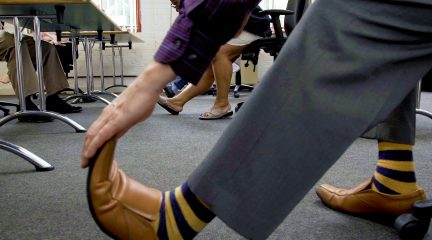 A floor-level shot of people doing chairobics in their workplace, stretching out their calf muscles