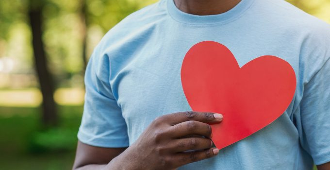 Man in blue t-shirt holding red paper heart to his chest