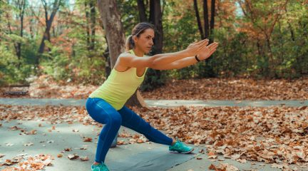 A woman doing side lunges outdoors with autumn leaves around her