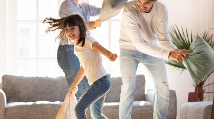 Two parents and a daughter have a pillow fight in the living room