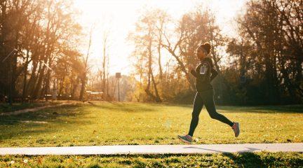 A woman runs through a park in full workout gear and headphones