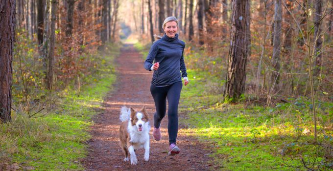 A fit older woman runs through the woods with her dog
