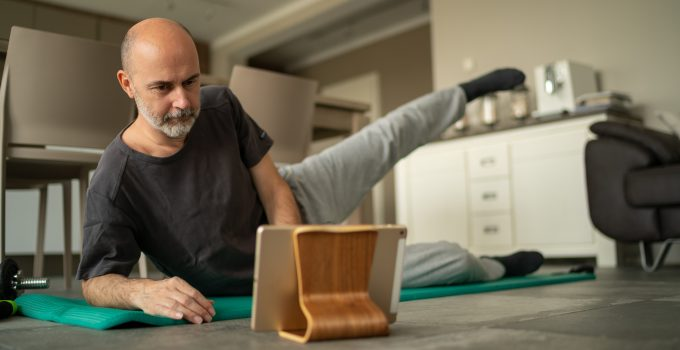 Older man doing yoga at home whilst watching iPad