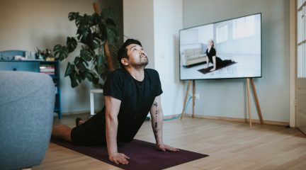 Young man stretching and following an online yoga class