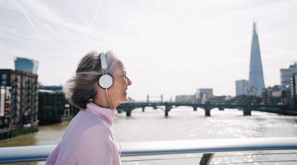 A senior woman running across a bridge in London listening to music