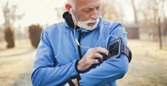 A senior man chooses his music from his sports armband before setting out on a run