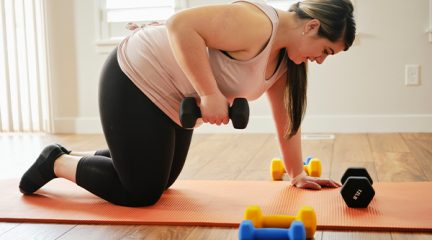 An overweight woman exercises at home using dumbbells