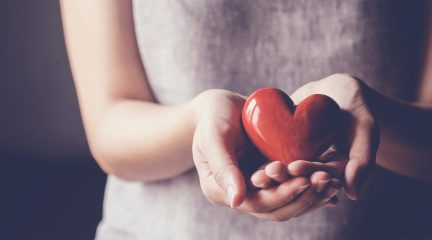 Woman holding a heart shaped object in her hands